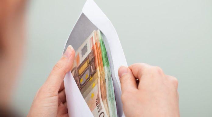 Mãos segurando um envelope cheio de euros. Custo de vida e média de salário na Irlanda