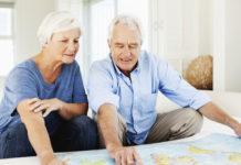 Casal acima de 50 anos escolhe o destino da próxima viagem em um mapa. Intercâmbio terceira idade.